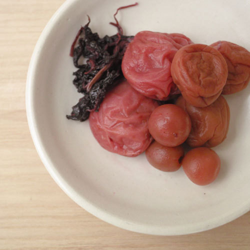 "musubook:  The pickled plum is a Japanese traditional food. ""Umeboshi"" in Japanese.  Which is dried in the sun after being preserved in salt. It is sour and is salty! So,rice and pickled plum are  very compatible."