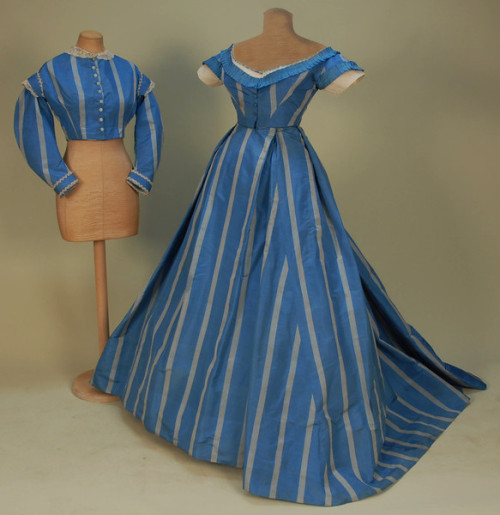 SILK TAFFETA GOWN with TWO BODICES, 1860's. French blue with wide grey stripe, day bodice with long collared sleeve, lace collar and cuff all trimmed in cream bobbin lace (all but one self button replaced with milk glass). Short sleeve evening bodice with open neck trimmed in pleated ribbon, white net and velvet ribbon, both bodices cut straight at waist. Voluminous trained skirt with large pleats, off center front closure, unlined, hem with deep stiffened backing below hooks & eyes to raise hemline by 3-4 inches.