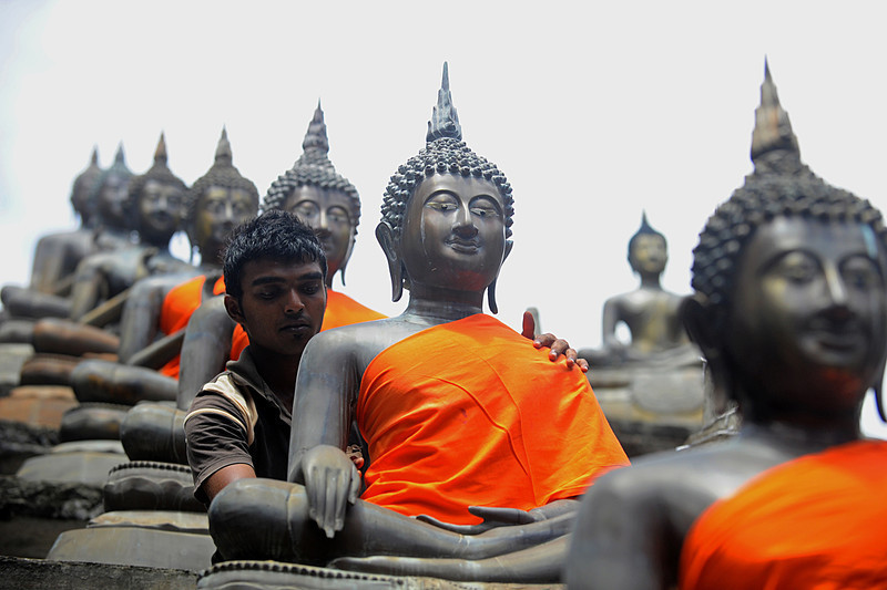 fotojournalismus:  A Sri Lankan man places a saffron robe over a Buddha statue at a temple in Colombo on May 22, 2013. Sri Lankan Buddhists are preparing to celebrate Vesak, which commemorates the birth of Buddha, his attaining enlightenment and his passing away on the full moon day of May which falls on May 24 this year. [Credit : Ishara S. Kodikara/AFP/Getty Images]