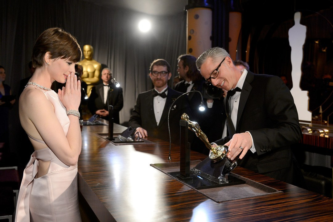 Anne Hathaway watches on as her name is engraved into her Oscar statue.
