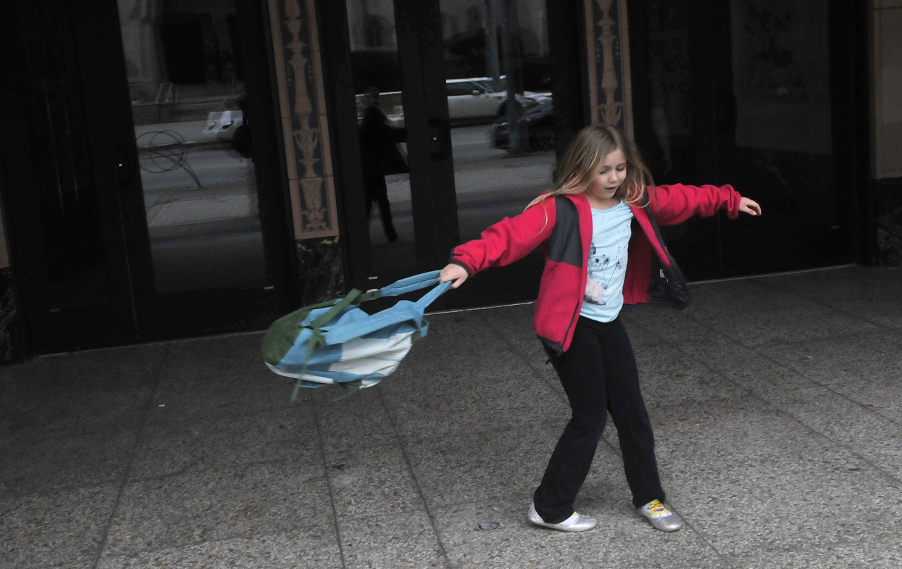 Virginia Schaffer, 8, twirls with her backpack in front of the Kelly-Strayhorn Theater in East Liberty as she waits to enter the theater for a rally against state education budget cuts. —Larry Roberts    Fore more pictures by Post-Gazette photographers, check out our Photos of the Day page