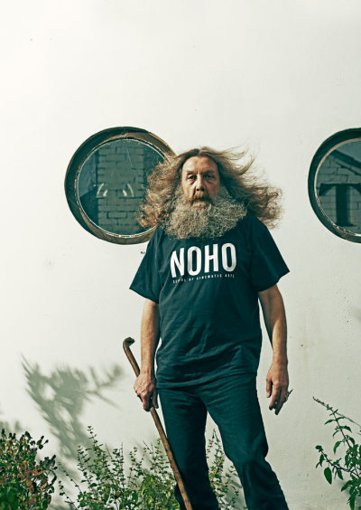 "guardian:   Alan Moore walks through Northampton town centre carrying a walking stick that's been sculpted to resemble a dangerous snake, and a hairbrush. The 59-year-old writer moves with a slight trip in his step, thus the cane, and keeps the brush to hand because he hasn't visited a barber since he was a teenager. For decades Moore has maintained his tremendous mane of hair, his wizard's beard, through bursts of aggressive combing. ""That way it tends to manage itself.""  Alan Moore, eccentric genius behind graphic-novel classics V for Vendetta and Watchmen, rejected big-movie riches. Now he has made a low-budget film in his beloved home town, Northampton"