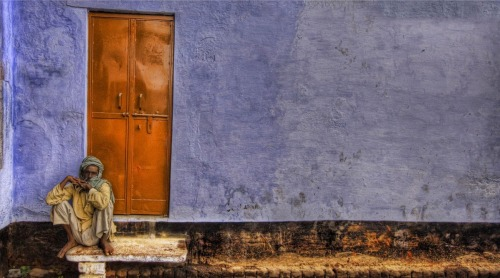 Trey Ratcliff Man sitting by door in the middle of the afternoon in northern India.
