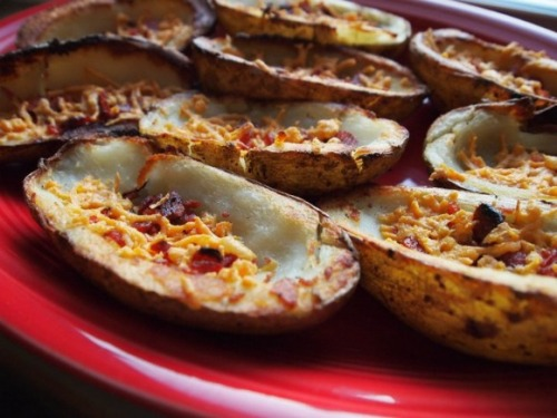 "Easy Game-Day Potato Skins Ingredients 6 potatoes  1 cup vegetable oil 8 oz. shredded vegan cheddar cheese (try Daiya brand) 1/8 cup soy bacon bits (try Bac-Os) 4 Tbsp. thinly sliced scallions Soy sour cream (optional) Instructions Preheat the oven to 375 F. Lightly grease a 9x13-inch baking pan. Pierce the potatoes with a fork and microwave on high until soft, approximately 10 to 13 minutes.  Remove from the microwave and cut in half vertically. Scoop out the inside, leaving a 1/4-inch-tick shell. Heat the oil to 365 in a deep fryer or on a deep saucepan. Fry the potato shells for 5 minutes. Remove and drain on paper towels.  Fill the potato shells with the ""cheese"" and soy bacon bits. Arrange on the prepared baking pan and bake for 10 to 15 minutes, or until the ""cheese"" has melted.  Top with the sliced scallions and the soy sour cream, if desired.  Enjoy!"