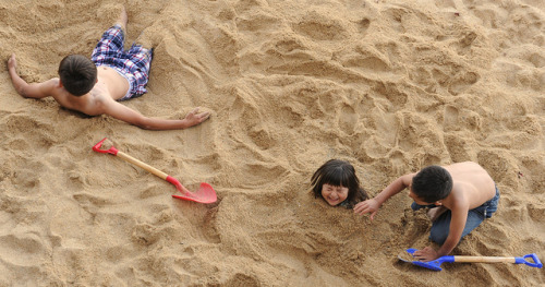 Buried up to her neck, a girl and her brothers play in the sand, shovels, sand angel, shade, Monterey, beach, California, USA on Flickr.