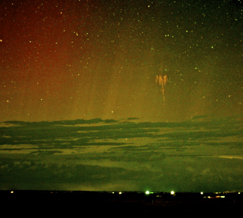 the-science-llama:  Red Sprite Lightning with Aurora  Explanation: What's that in the sky? It is a rarely seen form of lightning confirmed only about 25 years ago: a red sprite. Recent research has shown that following a powerful positive cloud-to-ground lightning strike, red sprites may start as 100-meter balls of ionized air that shoot down from about 80-km high at 10 percent the speed of light and are quickly followed by a group of upward streaking ionized balls. The above image, taken a few days ago above central South Dakota, USA, captured a bright red sprite, and is a candidate for the first color image ever recorded of a sprite and aurora together. Distant storm clouds cross the bottom of the image, while streaks of colorful aurora are visible in the background. Red sprites take only a fraction of a second to occur and are best seen when powerful thunderstorms are visible from the side.  Credit: APOD — Walter Lyons // FMA Research