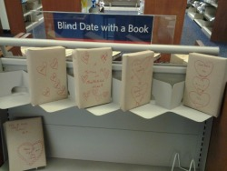 """My local library branch started doing this ""Blind Date with a Book"" thing, thought you guys might like it. The shelf was full when we got there, but was like this as we were leaving. The books are wrapped in paper and have different designs on them, and then a few words vaguely describing the subject matter of the book. Things like ""Drama"", ""Plot Twists"", ""espionage"", etc. The only thing exposed on the book is the barcode that you use to scan the book out. I thought it was a pretty cool idea."""
