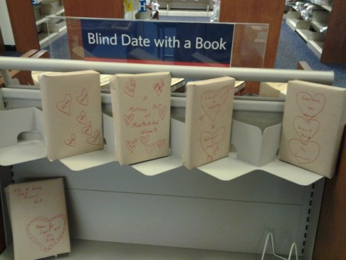 """My local library branch started doing this ""Blind Date with a Book"" thing, thought you guys might like it. The shelf was full when we got there, but was like this as we were leaving. The books are wrapped in paper and have different designs on them, and then a few words vaguely describing the subject matter of the book. Things like ""Drama"", ""Plot Twists"", ""espionage"", etc. The only thing exposed on the book is the barcode that you use to scan the book out. I thought it was a pretty cool idea.""   this makes my heart warm"