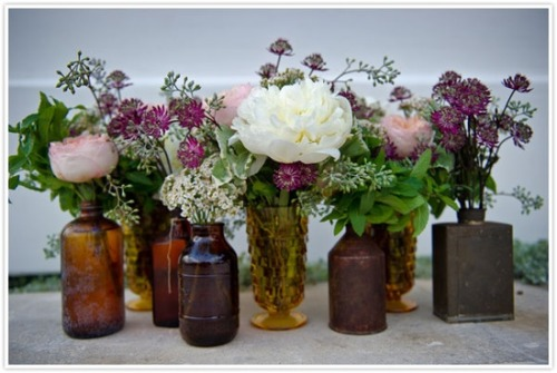 eclectic floral centerpiece - pink, purple, and white flowers in vintage bottles and vases