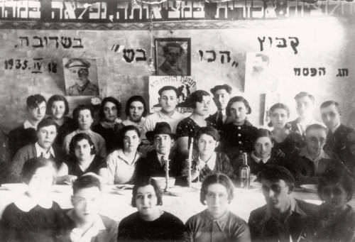 Kibbutz 'HaKovesh' celebrating the Passover Seder,  Seduva, Lithuania, April 18, 1935 Esther Orlin is standing third from left. Masha Shulman is standing fouth from right. The words in the background read: 'Pioneering is a cruel reality, but its essence is wonderful'