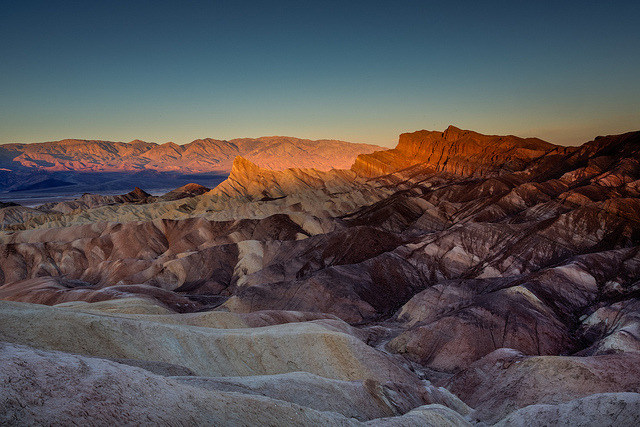 Zabriskie Point on Flickr.Via Flickr: It was Saturday morning and I was about to embark on my 18 hour journey back to Colorado. Originally I planned to drive my buddy back to Reno and stop in Lake Tahoe for sunset. But after looking at weather and road conditions, I knew that was not a good option. The lower route it won and my buddy Laith decided to fly. After sitting in 2mph traffic for a few hours I knew I was going to mis sunset completely and started planning for sunrise. A few people on G+ helped me out with locations in Death Valley, as I knew nothing and it was too spur the moment to plan ahead. I got to the parking lot at Zabriskie Point at 11pm and just slept in my car. It was around 37 to 47 degrees out, so it wasn't the best car camping conditions! But waking up and walking a few hundred feet up this hill, to see this, was definitely incredible. It sure is weird driving in to a place in complete darkness and and waking up to see where you ended up. Unfortunately there were no clouds but the light here was great. Now its time to shoot in some snowy conditions! Happy Holidays everyone!