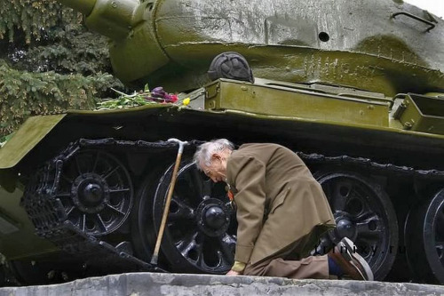 A Russian war veteran kneels beside the tank he spent the war in, now a monument.