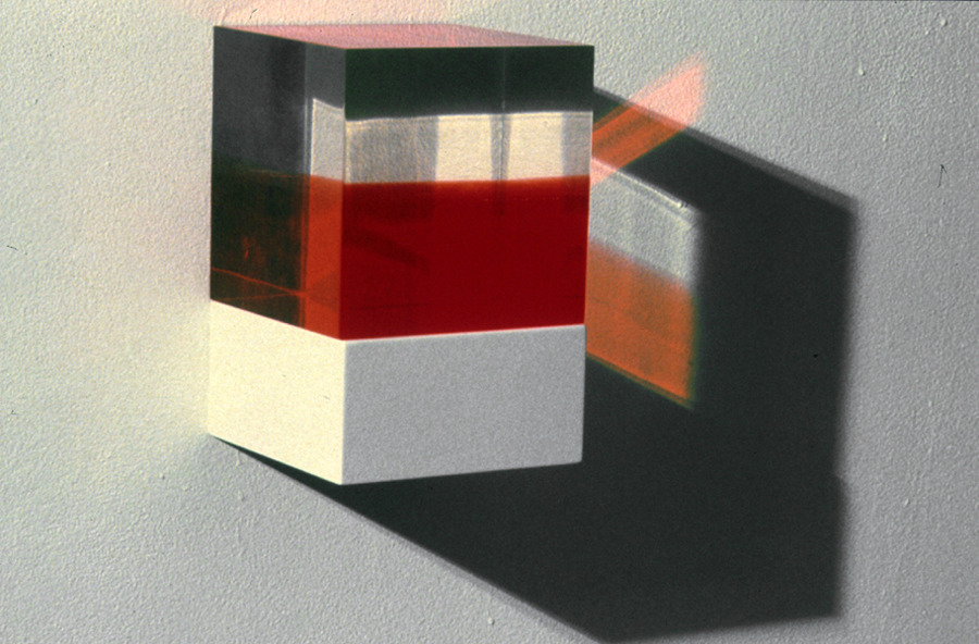 Self-portrait as a Lucite cube divided proportionally a (red) volume representing life lived and a (clear) volume representing life to come, based on statistical life expectancy.   |    Micah Lexier