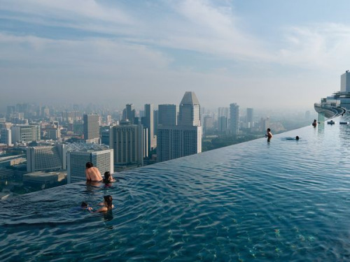 "travelhighlights:  Infinty Pool by Chia Ming Chien From National Geographic flickr:  The vertiginous ""infinity pool"" at the Marina Bay Sands resort offers a sweeping view of Singapore, a country that's achieved success while building up instead of out.  Singapore"