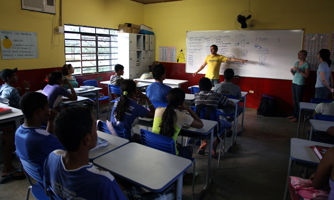 Ethan Shirley, a member of the Pantanal Partnership teaches a class to Brazilian students at a school in Congas. The U-M Water Systems team, which is part of the Pantanal Partnership organization on the UM campus, conducts a series of workshops in a village of Congas, on the edge of Pantanal, the largest wetlands in the word.  University of Michigan students teach kids from a local school the importance of clean drinking water and will build a sand based water filter together. They hope that the kids will in turn educate their parents about the water issues and that better water sanitation will help alleviate a number of serious diseases that plague the area.  Congas, Brazil.    Photo by Marcin Szczepanski/University of Michigan, College of Engineering, Multimedia Producer