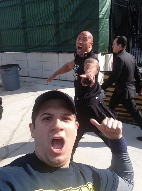 kneelift:  The Rock somehow manages to photobomb someone's candid photo of him.