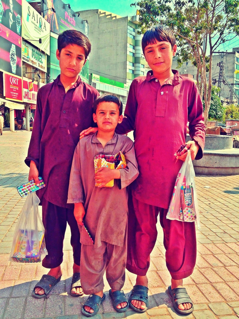 Little boys selling smarties in Liberty Market. Lahore, Pakistan