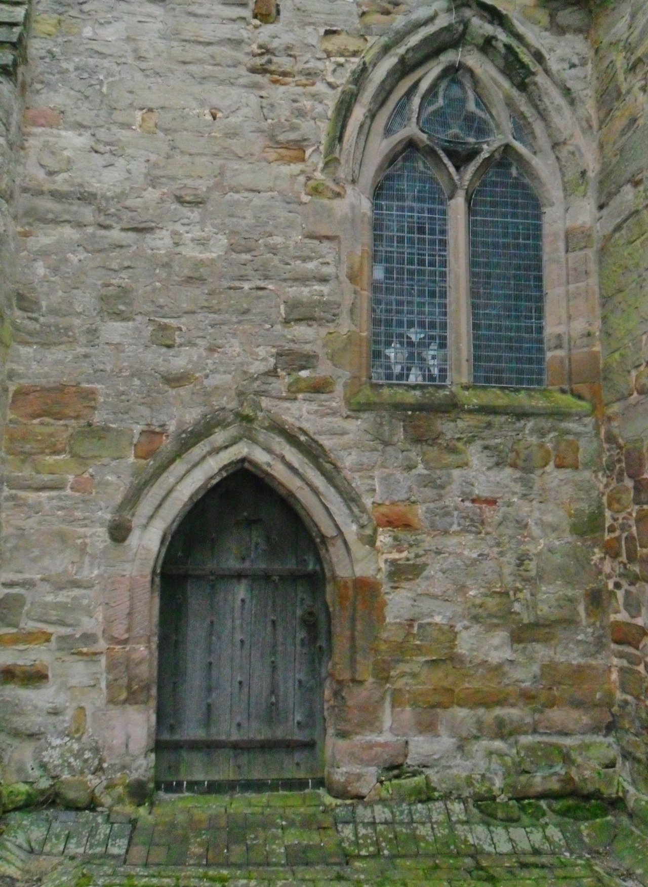 Eroded arched doorway and window of the 12th Century parish Church of St Peter & St Paul at Kingsbury, Warwickshire, England