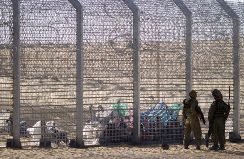 "Israel completes most of Egypt border fence The barrier aims to prevent illegal immigrants, drugs and weapons from making their way from Africa into Israel. Two years after construction began, Israelhas finished the bulk of the work on a fence along its border with Egypt. Closing off the rambling, 140-mile-long stretch of desert border will prevent the ""unfettered flow of illegal infiltrators, the smuggling of drugs and weapons,"" said a statement from the Defense Ministry, which oversaw the $400-million engineering project. Speaking at a ceremony marking the completion of the main section, Prime Minister Benjamin Netanyahu praised the effort to curb the illegal entry of migrants from Africa, reduced from more than 2,000 a month in January 2012 to fewer than 40 in December. Stopping the migrants is one aim of the fence, which stands about 15 to 20 feet high and includes multiple layers of barbed wire, communications equipment, a patrol road and asphalt track. It is similar to portions of the barrier that seals off the occupied West Bank from Israel, although that fence includes sections of concrete wall. Early last year, Netanyahu said Israel would build a similar fence along the desert border with Jordan. The government says all African migrants entering Israel illegally in recent months have been placed in detention facilities before reaching Israeli cities, where an estimated 60,000 migrants and asylum seekers — widely called ""infiltrators"" — already live. ""Just as we have stopped infiltration into Israeli cities, so too we shall succeed in the next mission, repatriating the tens of thousands of infiltrators to their countries of origin,"" Netanyahu said. He recently appointed Hagai Hadas, a former Mossad official, to oversee repatriation efforts. Israel deported nearly 4,000 Africans in 2012, but more sweeping repatriation could be difficult. Many migrants hail from war-torn areas or from countries that have no ties with Israel, according to Sigal Rozen, an official with a local migrant assistance organization. The influx of African migrants, most of whom slipped across the Egyptian border, has became a divisive social and political issue, as Israelis from already-disadvantaged areas express resentment toward the foreigners and politicians warn of a demographic threat. The tension has boiled over on several occasions in recent years, with demonstrators calling for the deportation of the Africans and extremists committing hate crimes, including firebombings of migrants' houses last spring. Pictured: African refugees sit on the ground behind a border fence after they attempted to cross illegally from Egypt into Israel, as Israeli soldiers stand guard near the border with Egypt, in southern Israel.(Ariel Schalit / Associated Press / September 4, 2012)"