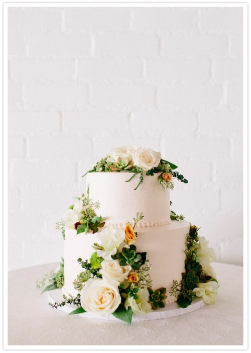 white wedding cake with roses and succulents