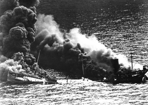 An Allied tanker torpedoed by German submarines begins to sink below the surface under the heat of fire during the Battle of the Atlantic, 1942.