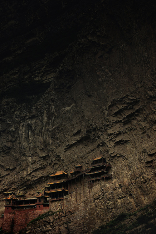 uncommonjones:  The Hanging monastery by Andrea Cavallini Photographer's Note: The Hanging Monastery is a temple built into a cliff near Datong, China. Built more than 1,500 years ago, this temple is notable not only for its location on a sheer precipice but also because it includes Buddhist, Taoist, and Confucian elements. The structure is kept in place with oak crossbeams fitted into holes chiseled into the cliffs.