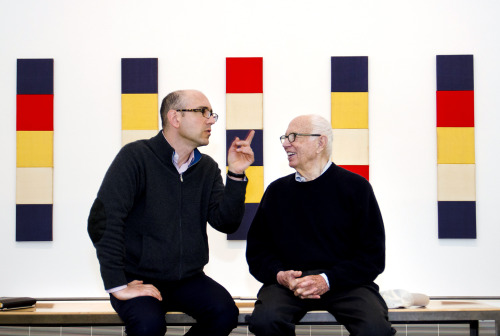 "Feeling good at 90: Spry soon-to-be-nonagenarian Ellsworth Kelly enjoys a moment with Carlos Basualdo, The Keith L. and Katherine Sachs Curator of Contemporary Art, in the Museum's newest installation, Homage to Ellsworth Kelly, in galleries 172 and 175. Background image: ""Red Yellow Blue White,"" 1952, by Ellsworth Kelly © Ellsworth Kelly"