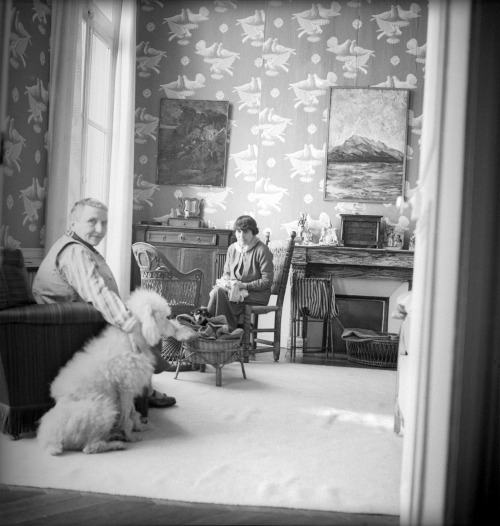 Gertrude Stein and Alice B. Toklas in a wallpapered room, 1938.