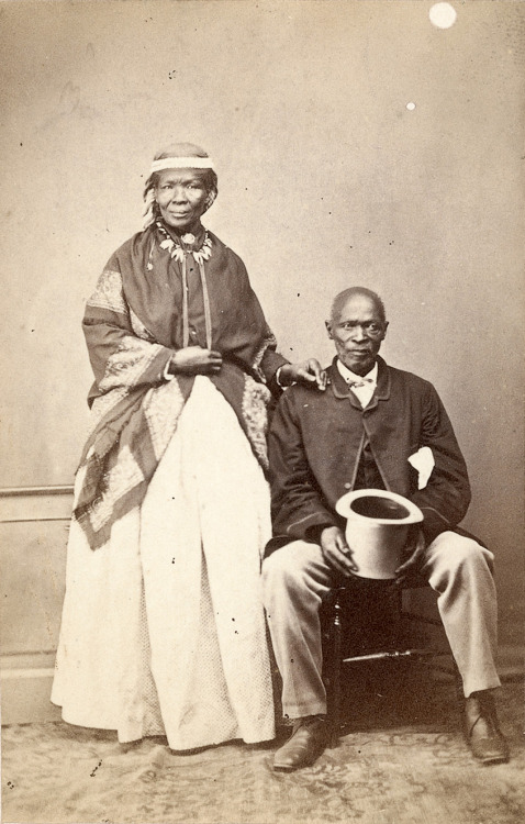 "NOTABLE AFRICANS: William Moore (attr.), inscribed: ""Macomo and his chief wife,"" South Africa, c. 1869. Along with several other Xhosa leaders and their wives, Maqoma was imprisoned on Robben Island for leading insurgencies during the Frontier Wars of the eighteen-fifties. This widely circulated portrait was taken after their release. Even when they were photographed on Robben Island, Maqoma and his wife never sat for the camera without dress coats, hats, and shawls."
