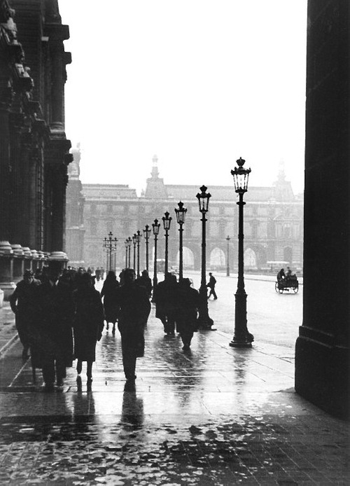 view of rain-swept pedestrians as they walk past the palais du louvre (on the left) towards a trio of arches that lead to the pont du carrousel, paris, 1937 photo by fred stein