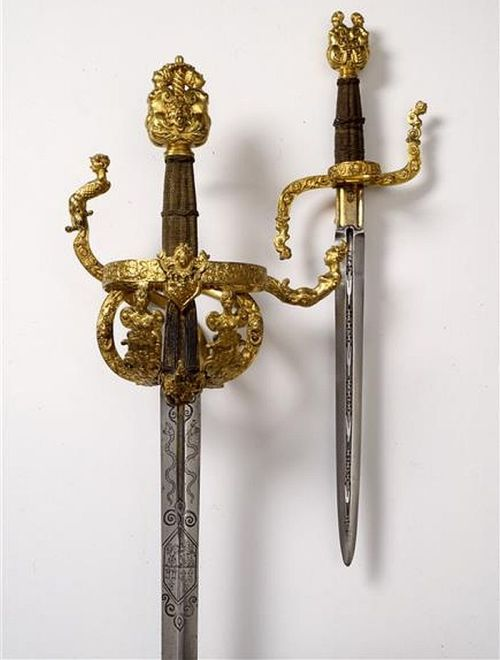 art-of-swords:  Ceremonial Weapon Set Composed of a rapier and dagger with scabbards Dated: probably 1610 Culture: German, Dresden Medium and Technique: flattened, cast, cut, engraved and gilded, blade, gold-plated brass wire wrapped handle Measurements: overall length 40.5cm blade 27.5cm; Weight 400g The pommel features two heads leaning against each other, two angel heads facing sideways. The quillons end in the shape of a Roman warrior and a female figure.  Source: © Staatliche Kunstsammlungen Dresden 2013