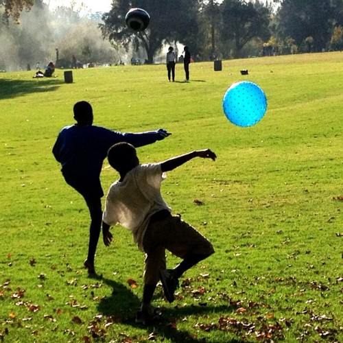 Two boys kicking balls at  Zoo Lake Park, Johannesburg, on May Day, a national holiday  Photo by Sara Terry, 1 May 2013. #maydayholiday, #saraterry13