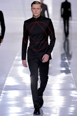 edit0real:  Dior Homme Fall/Winter 2013  Kris Van Assche created a minimal and futuristic Fall/Winter 2013 collection for Dior Homme, featuring clean lines, and space exploration inspired clothes all modeled in a white and immaculate room. An enigmatic sign was present on sweaters and jackets: a triangle held inside a circle.