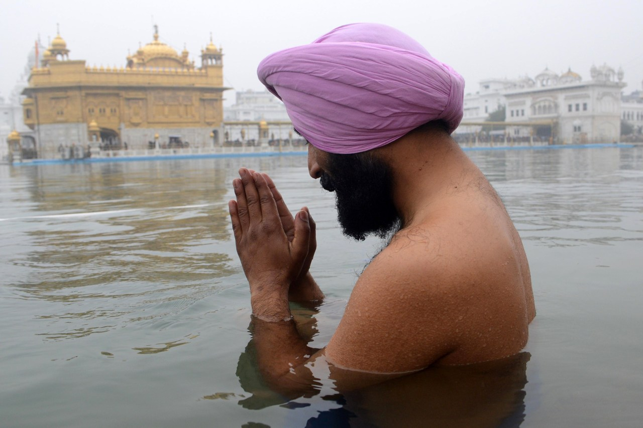 Sikh New Year. An Indian Sikh devotee prays as he takes a holy dip in the sarover - water tank  - at the Sikh Shrine Golden Temple in Amritsar. Thousands of Sikh devotees from across India and abroad are preparing to pay obeisance on the occasion of New Year at the temple in northern India. Nouvel an Sikh. Un indien de confession Sikh prie immergé dans le Sarover, réservoir d'eau dans le temple saint de Shrine Golden à Amristar. Des milliers de Sikhs venant de toute l'Inde et d'ailleurs se préparent à payer leur tributs lors du nouvel an dans ce temple sacré situé dans la région Nord de l'Inde.  PHOTOGRAPHER :AFP PHOTO/NARINDER NANU