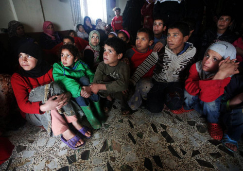 What next for Syria's refugees? Join Guardian global development's live panel discussion on Syria's humanitarian crisis from 1-2.30pm GMT. Photo: Syrian refugee children watch television at a temporary shelter, after their tents flooded from the rain, at a refugee camp, in the eastern Lebanese Town of Al-Faour near the border with Syria, Lebanon. Hussein Malla/AP