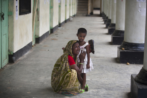 fotojournalismus:  A Bangladeshi woman reacts holding her son's daughter after her son's body was found after the April 24 garment factory building collapse in Savar, near Dhaka on May 12, 2013. [Credit : Ismail Ferdous/AP]