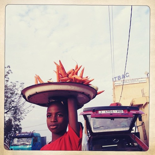 A young boy sells carrots outside of a bus station on the outskirts of Bamako, Mali on January 26. Photo by @glennagordon  #mali #bamako #trade #carrots #vegetables #kids #westafrica #transport #bus
