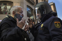 A policeman communicates with a demonstrator by a cordoned off street, during a protest against Spanish Citizens Security Law in Madrid, Spain, Saturday, Dec. 20, 2014. Thousands of people have gathered in several Spanish cities to protest against a new law that sets hefty fines for offenses such as burning the national flag and holding demonstrations outside parliament buildings or strategic installations. Also can be fined protesters who prevent authorities from carrying out evictions, insulting a police officer and disseminating photographs of police officers that endanger them or police operations. The legislation also allows for the summary expulsion of migrants entering the country's North African enclaves illegally. (AP Photo/Andres Kudacki) Read more: http://www.dailymail.co.uk/wires/ap/article-2881882/Spanish-protest-nations-new-security-law.html#ixzz3Mdk3FFUE