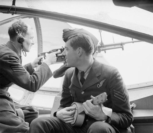 """On board a No 240 Squadron Catalina at Stranraer, March 1941. A WOp/AG (wireless operator/air gunner) poses with his twin Vickers 'K' guns at the starboard blister hatch, while being serenaded by the banjulele-playing navigator!"" (via)"