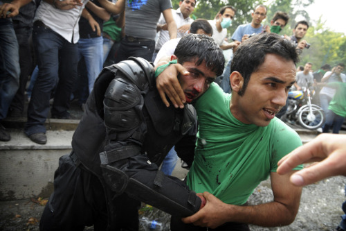 A backer of Mir Hossein Mousavi helps evacuate an injured riot-police officer during riots in Tehran on June 13, 2009. — OLIVIER LABAN-MATTEI/AFP/Getty Images