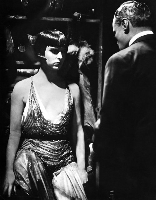 "Louise Brooks & Fritz Körtner in Pandora's Box (1929, G.W. Pabst) (via drmacro) Louise Brooks on the outrage that followed the release of Pandora's Box: ""Besides daring to show the prostitute as the victim; Mr. Pabst went on to the final damning immorality of making his Lulu as ""sweetly innocent"" as the flowers which adorned her costumes and filled the scenes of the play…So it is that my playing of the tragic Lulu with no sense of sin remains generally unacceptable to this day. Three years ago, after seeing Pandora's Box at Eastman House, a priest said to me, ""How did you feel? Playing that girl!"" ""Feel? I felt fine! It all seemed perfectly normal to me."" Seeing him start with distaste and disbelief, and unwilling to be mistaken for one of those women who like to shock priests with sensational confessions, I went on to prove the truth of Lulu's world by my own experience in the 1925 Follies, when my best friend was a lesbian and I knew two millionaire publishers, much like Schoen in the film, who backed shows to keep themselves well supplied with Lulus. But the priest rejected my reality exactly as Berlin had rejected its reality when we made Lulu and sex was the business of the town. At the Eden Hotel, where I lived in Berlin [while filming Pandora's Box], the café bar was lined with the higher-priced trollops. The economy girls walked the streets outside. On the corner stood the girls in boots, advertising flagellation. Actors' agents pimped for the ladies in luxury apartments in the Bavarian Quarter. Race-track touts at the Hoppegarten arranged orgies for groups of sportsmen. The nightclub Eldorado displayed an enticing line of homosexuals dressed as women. At the Maly, there was a choice of feminine or collar-and-tie lesbians. Collective lust roared unashamed at the theater. In the revue Chocolate Kiddies, when Josephine Baker appeared naked except for a girdle of bananas, it was precisely as Lulu's stage entrance was described by Wedekind: ""They rage there as in a menagerie when the meat appears at the cage."" I revered Pabst for his truthful picture of this world of pleasure which let me play Lulu naturally. The rest of the cast were tempted to rebellion. And perhaps that was his most brilliant directorial achievement-getting a group of actors to play characters without ""sympathy"", whose only motivation was sexual gratification."""