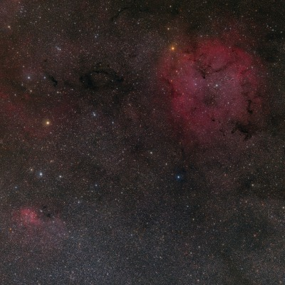 Sprawling across hundreds of light-years, emission nebula IC 1396, visible on the upper right, mixes glowing cosmic gas and dark dust clouds.  Stars are forming in this area, only about 3,000 light-years from Earth.  This wide angle view also captures surrounding emission and absorption nebula.    The red glow in IC 1396 and across the image is created by cosmic hydrogen gas recapturing electrons knocked away by energetic starlight.  The dark dust clouds are dense groups of smoke-like particles common in the disks of spiral galaxies.  Among the intriguing dark shapes within IC 1396, the winding Elephant's Trunk nebula lies just right of the nebula's center.  IC 1396 lies in the high and far off constellation of Cepheus.