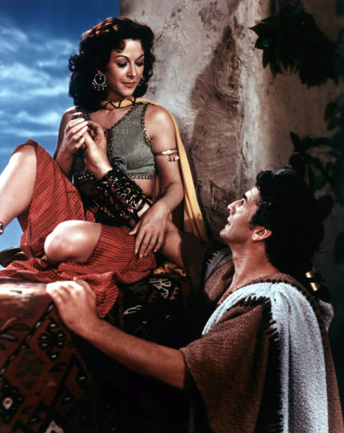 "Hedy Lamarr & Victor Mature in Samson & Delilah (1949, dir. Cecil B. DeMille) In her lively 1967 autobiography, Ecstasy and Me: My Life as a Woman, Hedy Lamarr recalls having cocktails at Romanoff's with a sleazy talent scout (whom she pseudonymously refers to as Sidney), who tries to seduce her by offering her an audience with Cecil B. DeMille, who was in the process of casting Samson and Delilah. ""C.B.'s a genius at those things,"" Sidney says, ""By the time he's through spreading the money and talent around, every man in the world will want to screw the heroine of that particular biblical drama. It's a natural; a guy with muscles, a broad with virginity."" ""Who plays Samson?"" Lamarr asked. ""They're thinking of Victor Mature. But who cares? It's only a body to set you off in the ruins. Muscles and tits sugarcoated with religion. It's for you."" As repulsed as Lamarr was by Sidney's vulgar approach to filmmaking, she bit the carrot and met with the director. A few days later, the role was hers. Later, Lamarr's agent echoed Sidney's sentiments, ""C.B. is brilliant. When it comes to sex and spectacle, no one can tear down a temple and tear off a piece at one and the same time like he can. When he sells sex, sister, people buy because he wraps it in fancy paper with pink ribbons."" -Bret Wood, TCM (via)"