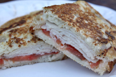 "Day 12: Turkey and tomato panini.  The lack of color in this photo bothers me. There was something green in my dinner, I promise! Well, I assembled these sandwiches an hour before I actually made them. I wouldn't suggest this normally - the tomatoes make the bread soggy - but I discovered to my chagrin that my loaf of bread was dry, so I figured ""What the hey?"" I wrapped them up and flattened them with a dictionary (I'm serious) because I couldn't be bothered to use two skillets and cans and whatever the recipe says, and Lord knows I don't own a panini machine. I bypassed yogurt in my spread simply because I didn't have any - and frankly, you don't need it. I'd suggest making an extra half-batch though (and maybe adding just a tad more basil). These were delicious. My family said ""These are the best paninis everrr!"" so you know they're good. Oh. If you listen to your brain instead of your stomach and choose to use wheat bread instead of Asiago sourdough bread, you will reduce this 310-calorie splurge to about 215 calories. :] So yum."