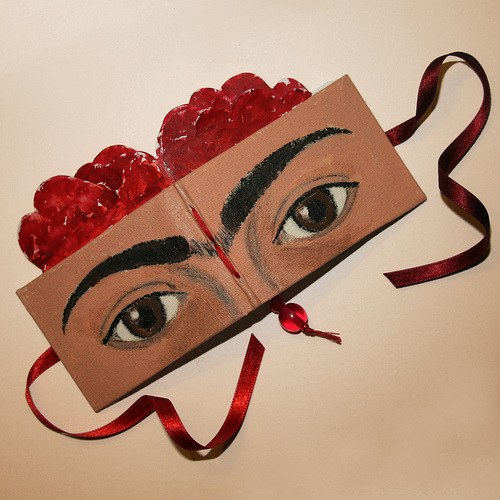 fridakahlorocks:  handbound mini book via paperfection  Frida Kahlo with her trademark unibrow, a stern and somewhat sad look in her eyes and roses in her hair.
