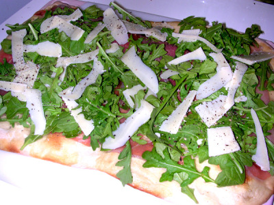 Recipe: Prosciutto, Arugula and Parmesan Flatbread Cured ham is good for the soul, this I am sure of. If you are not wrapping it around melon, asparagus or shoving it by the handfuls into your mouth, then you should give this really easy recipe a try. If the word aroogulla is sending your mind all scatter brained, no worries. This is a fabulous green rich in vitamin C, potassium and along with the rich spicy taste, is considered to be an aphrodisiac. Ingredients: 1 	 	ball Trader Joe's Pizza Dough 1/2 	cup 	Parmesan cheese, thinly shaved/sliced 6 	oz Prosciutto Extra-Virgin Olive Oil 1 	cup Arugula, rinsed and dried Fresh Ground Pepper Flour Instructions: Preheat your oven to 425 degrees. Add flour to a rolling surface such as a cleaned counter or cutting board. Place the ball of dough out and let it sit for about 20 minutes. Roll out the dough as best you can, trying to keep the surface even and the shape pleasing. When it is thinly rolled out place it on baking sheet or stone. Be sure to poke holes throughout the surface it to eliminate bubbles.  Bake dough for about 15 minutes, till it starts turning a nice golden brown. Remove from oven. Drizzle dough with olive oil. Line with prosciutto  Add arugula and Parmesan. Finally grind fresh pepper on top and enjoy!