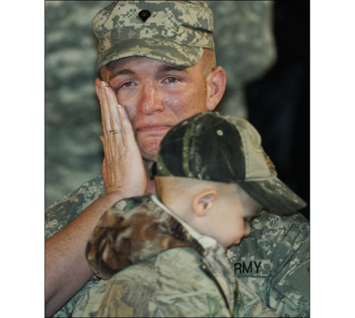 The Big Picture: Tears - Photo by Orlin Wagner/AP BBC NEWS: Travis Jones, of the 1st Infantry Division, has tears wiped by his wife as he is reunited with his two-year-old son upon his return from Iraq to Fort Riley, Kansas, USA, 27 September 2009.