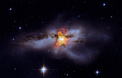 Supermassive Black Holes Collide to Become Even More Super and Massive  New X-ray data from NASA's Chandra X-ray Observatory added to an image previously captured by the Hubble Space Telescope created this amazing composite image of two black holes on the verge of colliding.  The two supermassive black holes, which show up as two points of light in the center of the galaxy NGC 6240, are only 3,000 light-years apart. Astronomers think the two will eventually combine into a single, larger black hole.  Also combining to make a whole greater than the sum of its parts are the two pieces of this image, shown below. Space photos are often a combination of multiple images and sets of data, designed to bring out the details and beauty of the subject. In this case, Chandra's X-ray data and Hubble's optical data come together to create an image so stunning that it looks like it must be an artist's rendering.