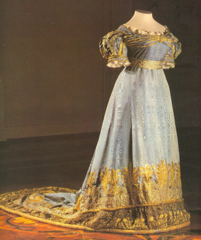 A Russian Imperial Court dress from the late Regency period of the 1820s. It is made of a blue silk moire, or watered silk, fabric. In reference to other Russian Court dresses, this one is moderately simple. It is interesting to see how the Court dress stayed true yet changed with the fashions at the same time. Notice how the layers of fabric and decoration at the hems and how they are weighted with what looks like piping (with a very large cord). This was all done by HAND! Back view: