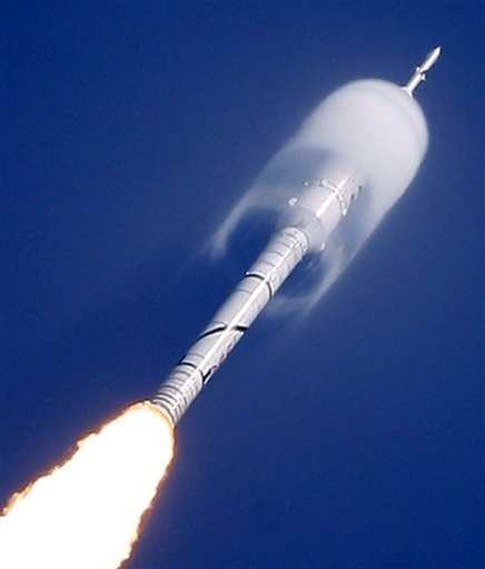 A cone of moisture surrounds part of the Ares I-X rocket during lift off (via AP)